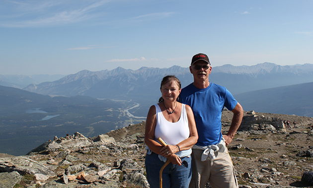 Photo of a couple at the top of Whistler's Mountain in Jasper, Alberta.