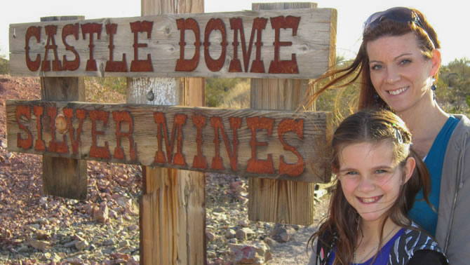 Mother and daughter Jena and Haley Jones stand in front of the Castle Dome Silver Mines sign.