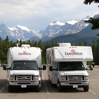 Photo two RV's with mountains in background