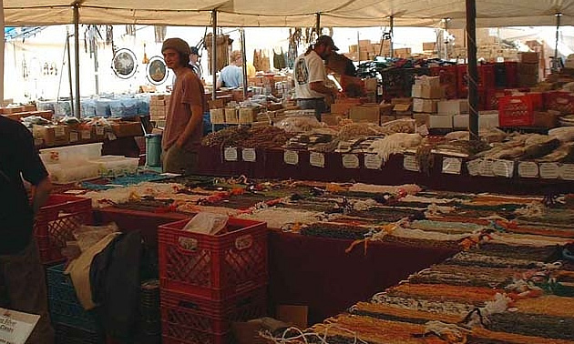 A man stands in an outdoor market, with tables full of handmade crafts.