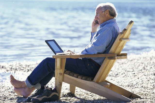 An elderly man sitting in a wooden beach chair talking on his cell phone.