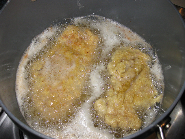 Flour coated chicken is frying in oil.