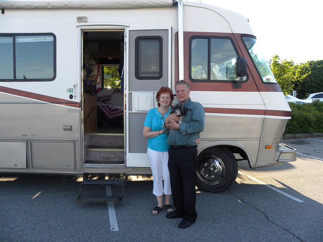 Barb and Dave Rees standing outside their rig with their little dog.