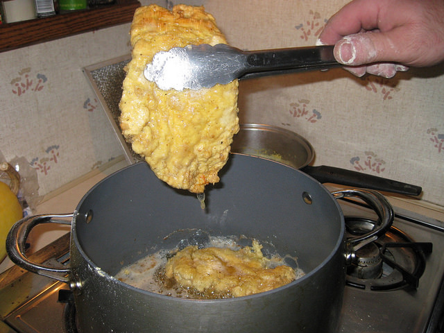 Removing the chicken when it is crispy and golden brown.
