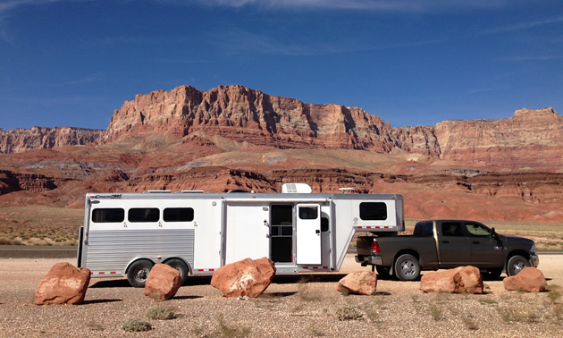 A gooseneck horse trailer with living quarters pulled by a black dodge truck.