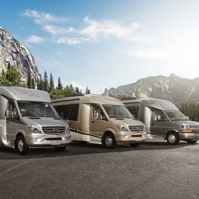 A line-up of Leisure Travel Vans, set against a backdrop of mountains.