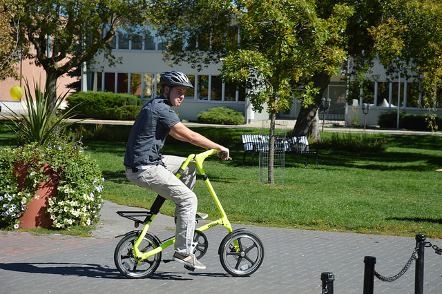 A young man riding a bright yellow Strida bike