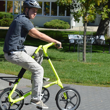 A young man riding a bright yellow Strida bike