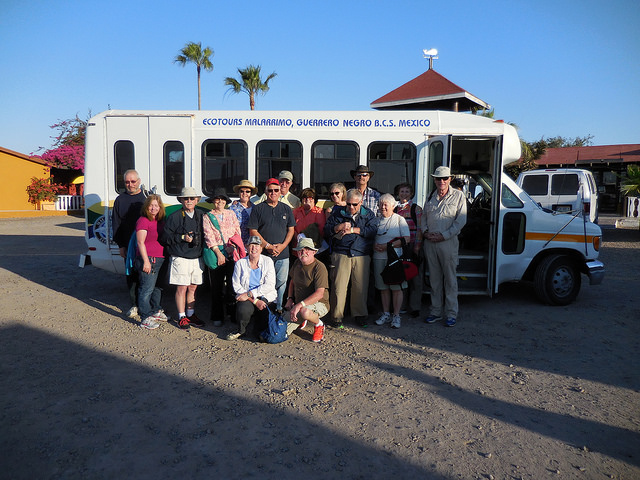 A group with Baja Amigos standing in front of a small tour bus ready to go on a tour.