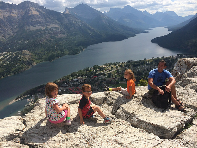 Minet 8, Myah and Mikey 6 together with their dad, Dave, are enjoying the rewarding view after their climb up the bear's hump at Waterton National Park.