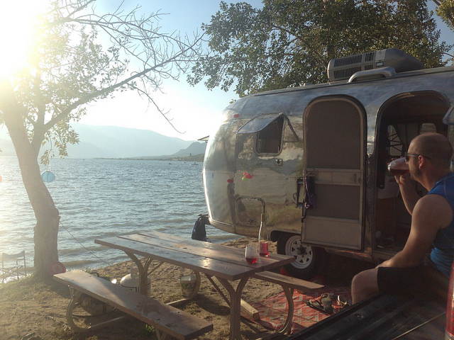 Dave Barton sitting in a lawn chair outside of his vintage airstream.  The airstream is parked on the edge of a lake
