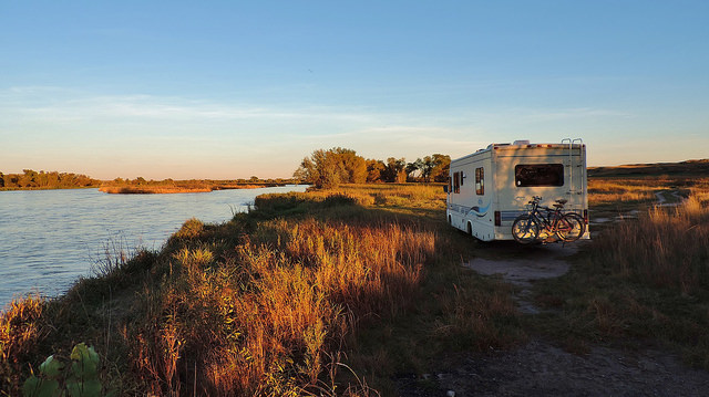 A photo of Sherman, the Read's motorhome next to a grassy river bank at sunset.