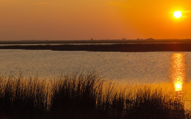 An orange sunset over the Last Mountain Lake National Wildlife Area and Migratory Bird Sanctuary.