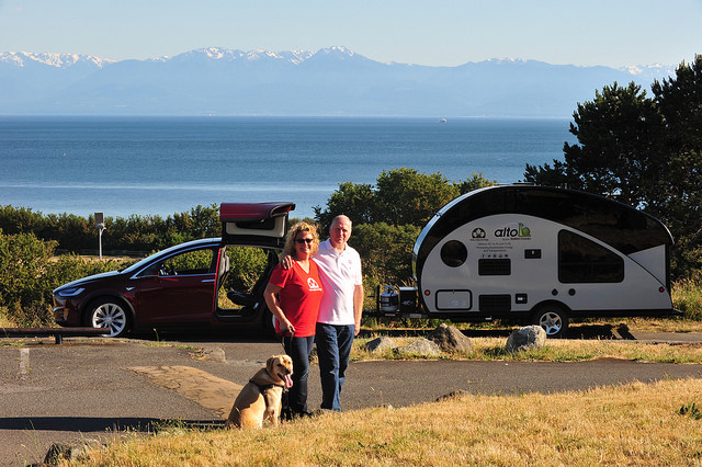 Oetter and Sommerfeld embark on a cross-country journey with their dog, Kye, as seen in this photo standing with their electric car and trailer behind them.