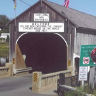Photo of a large covered bridge with a road going through it.