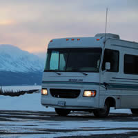 An RV on snowy road with snowy mountains in the background.