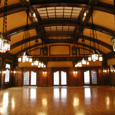 The Royal Alexandra Hall has a high, arched roof with wooden beams stretching across its ceiling. Bright, exquisite chandeliers hang low from up above.