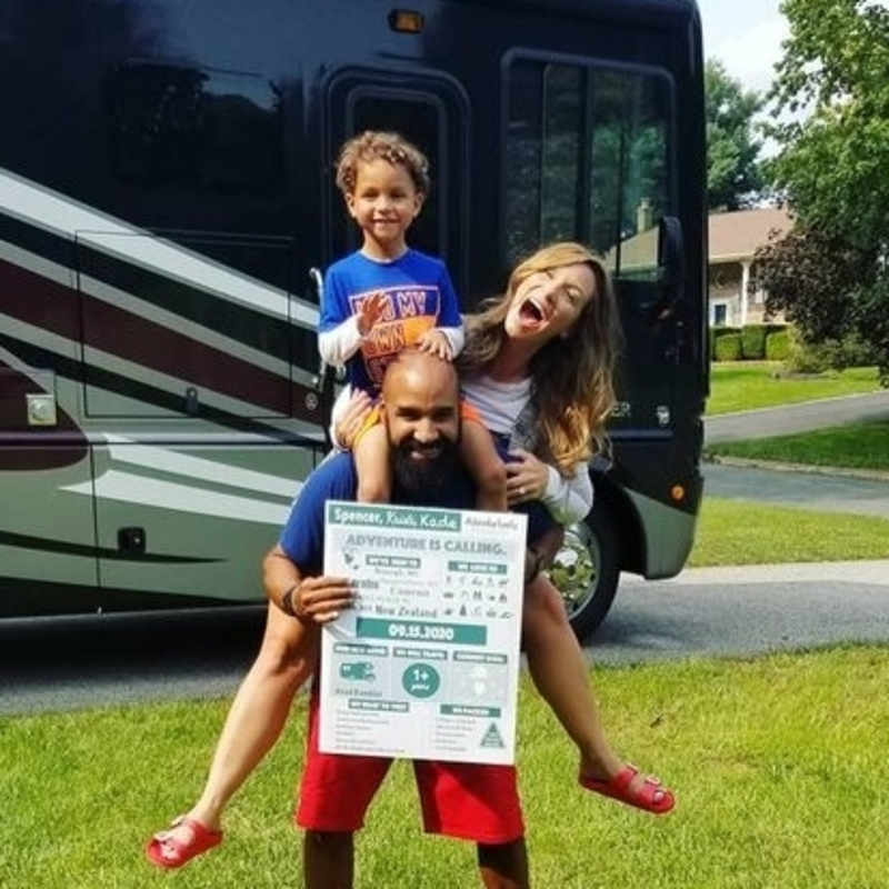 Family of three - mom, dad and child, in front of a Class A RV