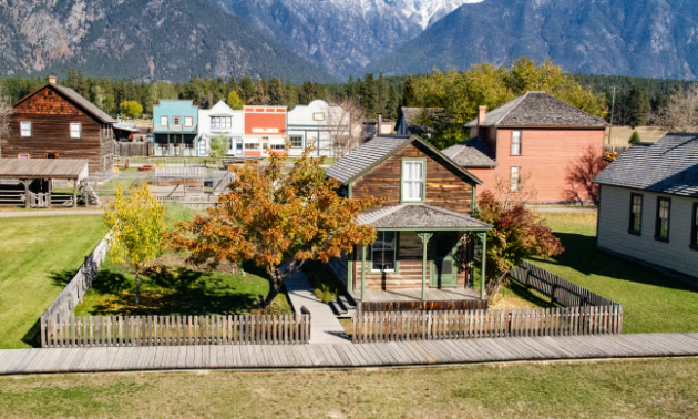 1890s-style homes and buildings reside in a rustic-looking environment with trees changing colours in fall