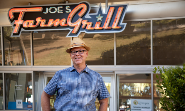 Joe Johnston, the owner of Joe's Farm Grill, a ranch-style family homestead restaurant, smiles in front of his business.