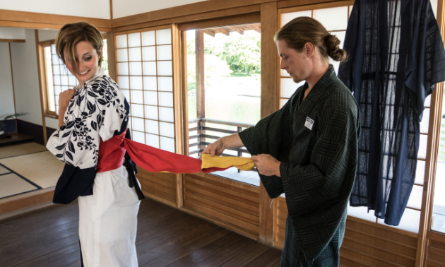 A man assists a woman with her formal Japanese attire.