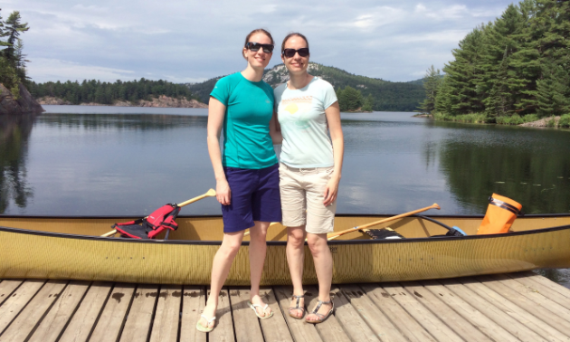 Two women wearing sunglasses, T-shirts, shorts and sandals smile in front of a backdrop that includes a yellow canoe, a lake, distant mountains and cloudy skies.