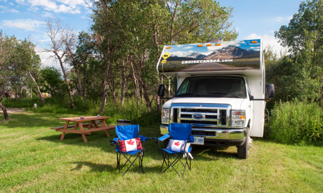 Two blue fold-out chairs face towards the camera with pillows that emblazon the Canada flag. A picnic table and RV are behind the chairs in a pleasant-looking green park area.