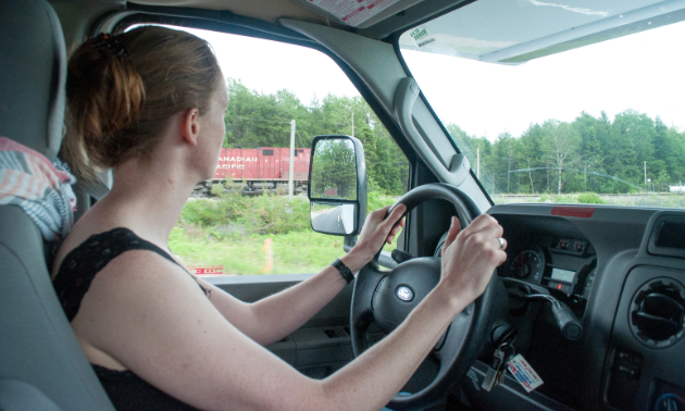 A woman drives an RV and takes her eyes off the road for a moment to look upon a Canadian fixture: a red Canadian Pacific train travelling on a parallel course.