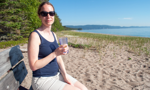 A woman wearing sunglasses, a tank top and shorts holds a beverage on a beach.