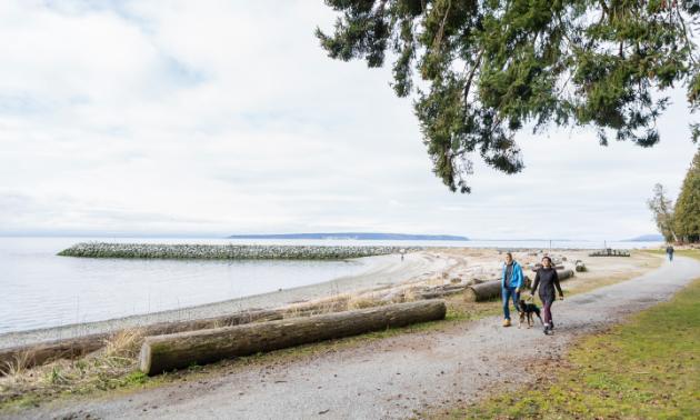 Two women take a dog for a walk along a shoreline.