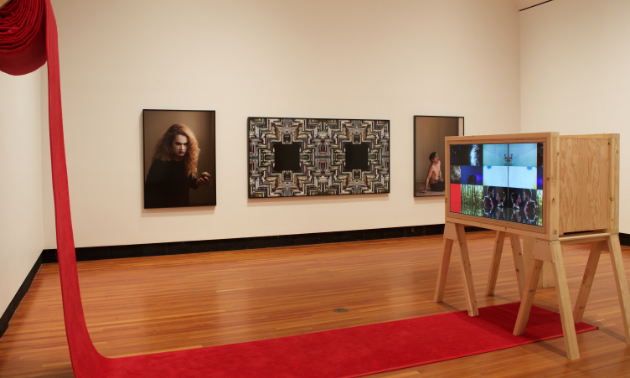 A red piece of cloth is draped off the wall onto part of the floor. A cabinet is propped up in the middle of the room. A mesmerizing portrait separates two odd photos.