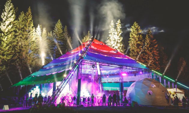 The Motion Notion Festival tent is lit up at night.