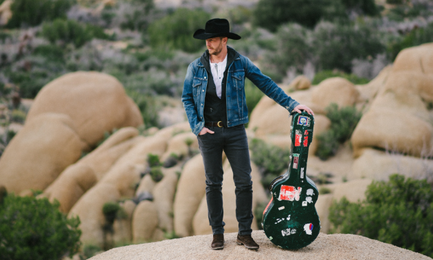 Paul Brandt poses with his guitar in the desert