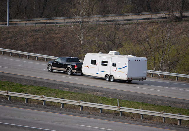 A picture of a pickup truck pulling a long white RV trailer on a highway.