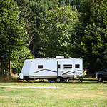 Picture of a  white RV trailer parked in a field with some trees behind it.