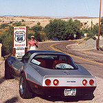 Picture of a Corvette stopped on the side of the Route 66 sign.