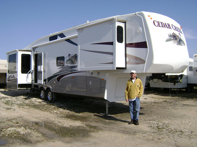 A man standing in front of his large RV home.