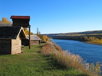 2 cabins on a bluff next to the river.