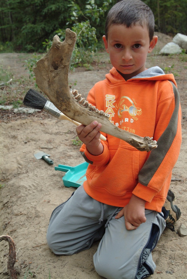 Little boy holding a jaw bone that he helped dig.