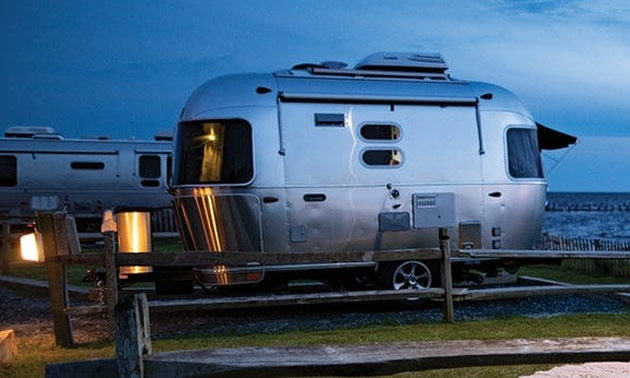 Airstream Caravel model parked at spot near ocean.
