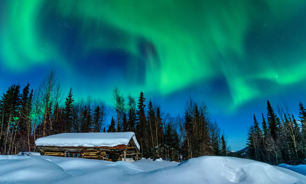 A cabin is buried in deep snow with northern lights in the sky.