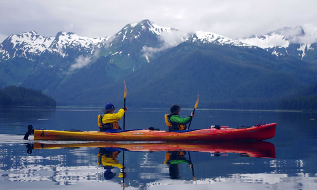 Two people are kayaking, with snowy mountains in the background.