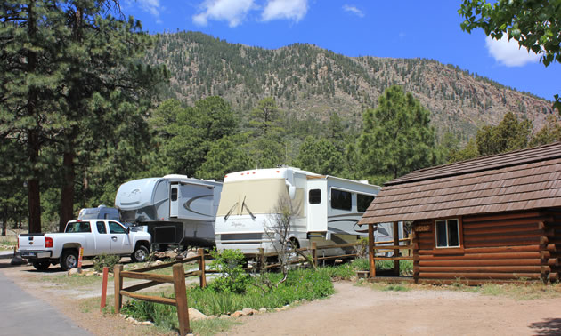 A campground in Arizona, with mountain in background and large RV parked in camping spot.