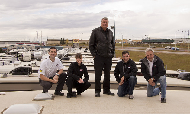 Staff of ArrKann Trailer & RV Centre pose on top of an RV at one of their two Edmonton locations (from left to right: Rob Minarchi, Sarah Baptiste, Ken Friedenberg, Paul Hopkins and Dave Hill).