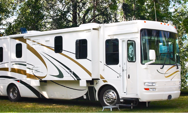 A large motorhome parked in a treed spot