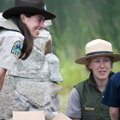 Picture of two park rangers interacting with a child.