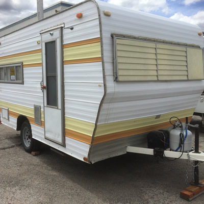 A yellow and brown striped trailer sitting on a sales lot.