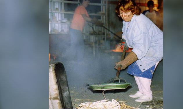 a woman using a large pitchfork to put a piece of raku pottery into a bed of straw to cool after being fired
