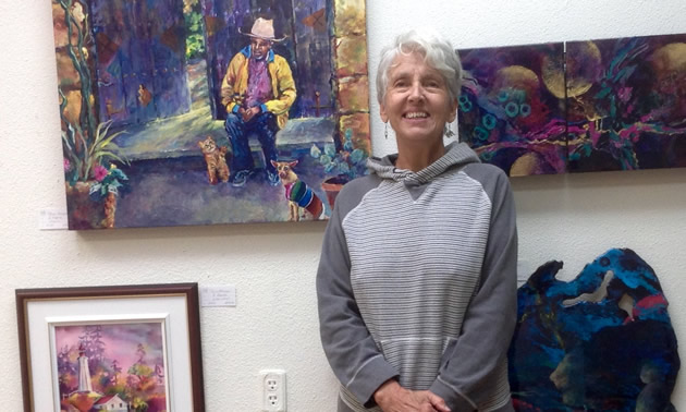 Bonny Roberts posed with some of her paintings on display at the Okanagan Art Gallery.