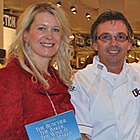 Woman in red, holding a book, stands with two men and a woman in chefs' wear, with a notice about a book signing.